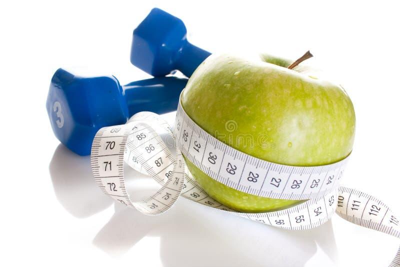Dumbbells, maçã verde fresca e fita da medida imagem de stock