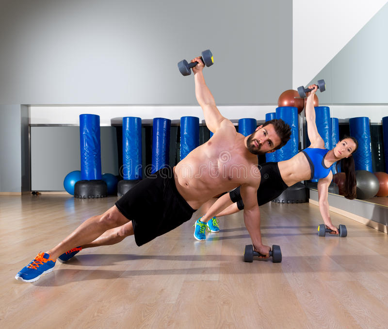 Dumbbells push-ups couple at fitness gym. Dumbbells push-ups pushups couple at fitness gym workout royalty free stock photos