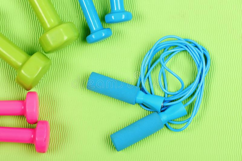 Dumbbells and skipping rope in cyan blue color. Shaping and fitness equipment. Healthy shape and sport concept. Dumbbells and skipping rope in cyan blue color on royalty free stock image