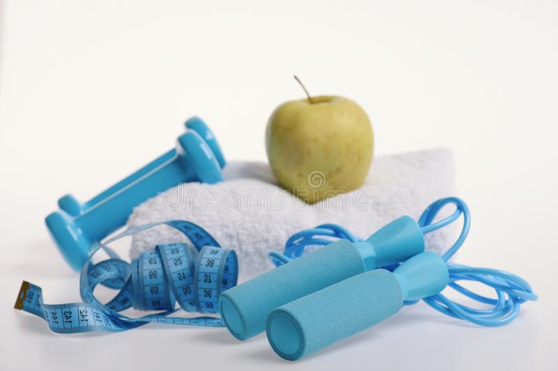 Dumbbells, skipping rope in cyan color near apple and towel. On white background. Health and fitness symbols. Jump rope, fruit, barbells next to blue measure royalty free stock photo