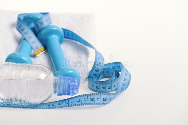 Dumbbells, skipping rope in cyan color near water bottle. Fit shape and sport concept. Health and fitness symbols. Dumbbells, skipping rope in cyan color near stock photography