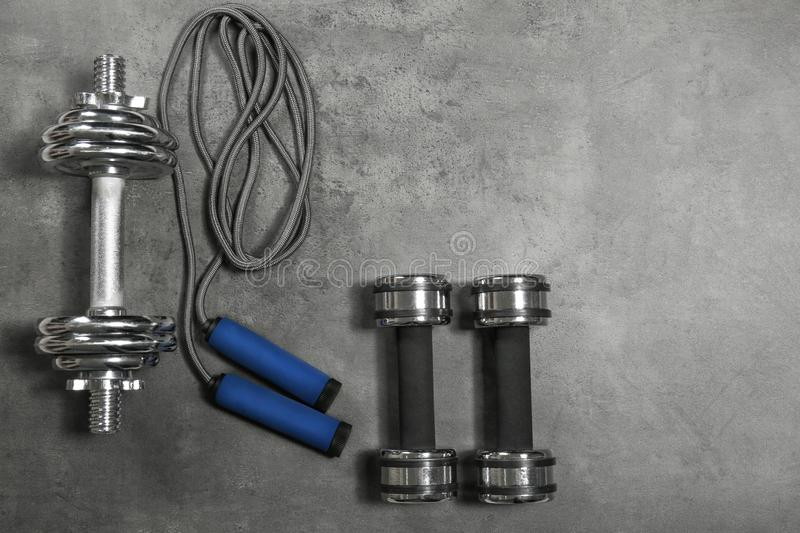Dumbbells and skipping rope. On grey textured background royalty free stock image