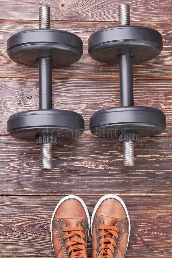 Dumbbells and sneakers, wooden background. stock photos
