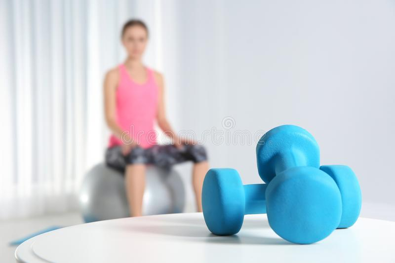 Dumbbells on table and woman doing fitness exercises at home. Space for text royalty free stock image