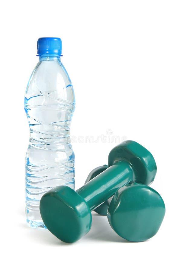 Dumbbells verdi e una bottiglia di acqua fotografia stock