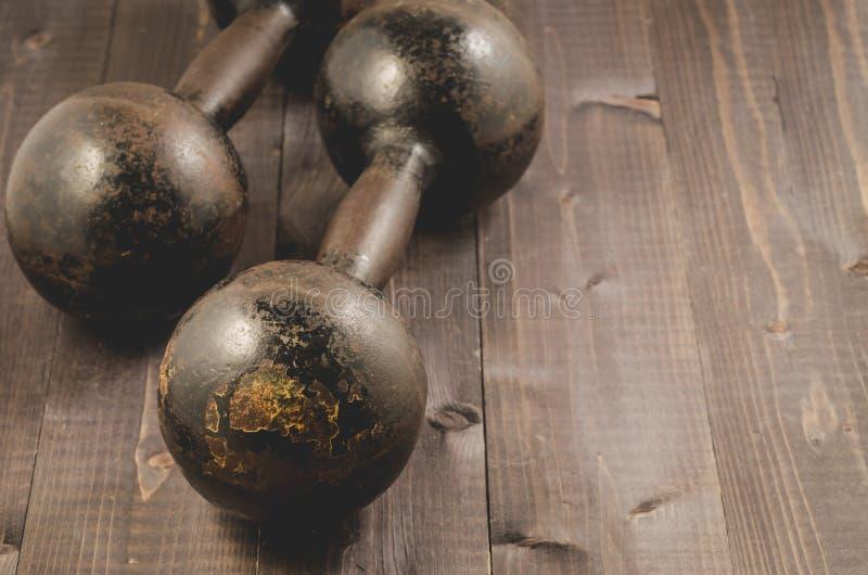 Dumbbells w gym, Dumbbells w sprawności fizycznej gym na ciemnym drewnie sprawności fizycznej/ obraz stock