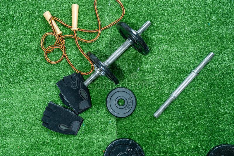 Dumbbells, weight discs, gloves and accessories for sport, on the grass, Fitness royalty free stock images
