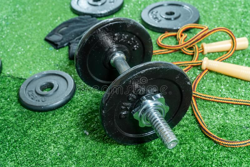 Dumbbells, weight discs, gloves and accessories for sport, on the grass, Fitness stock image