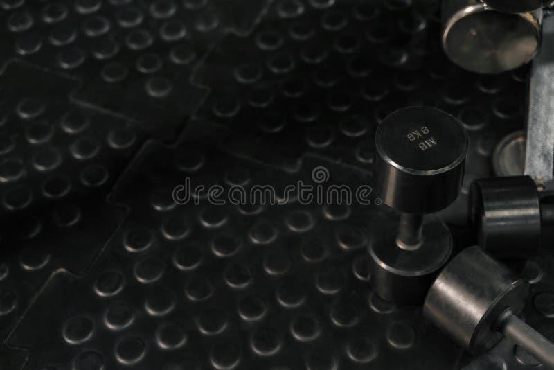 Dumbbels op vloer in een gymnastiek Crossfitmateriaal De ruimte van het exemplaar stock afbeeldingen