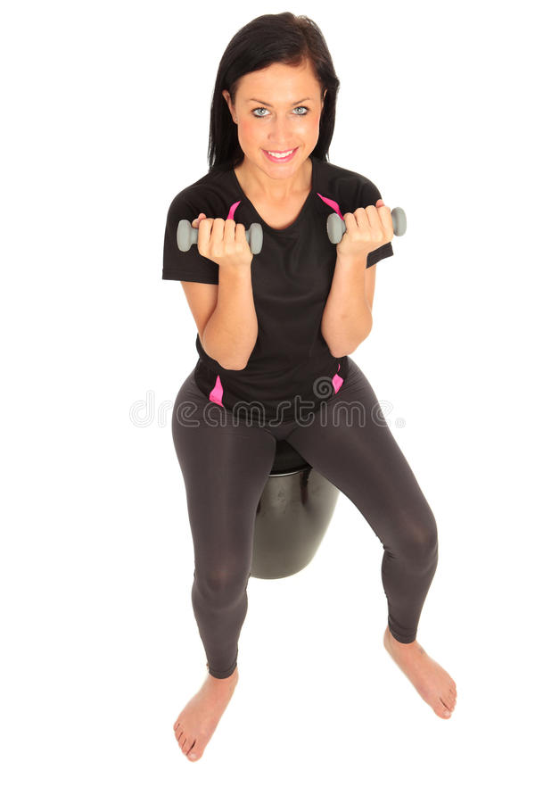 Dumbell Exercise. A young female dressed in sports clothes performing seated dumbell curl exercise royalty free stock images