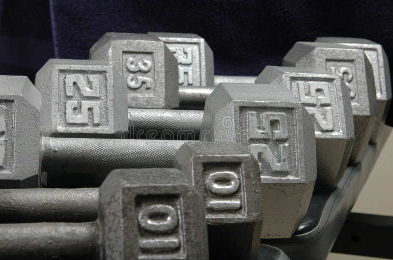 Dumbells. Different size dumbells are laid out on a weight bench with a towel hanging behind stock photography