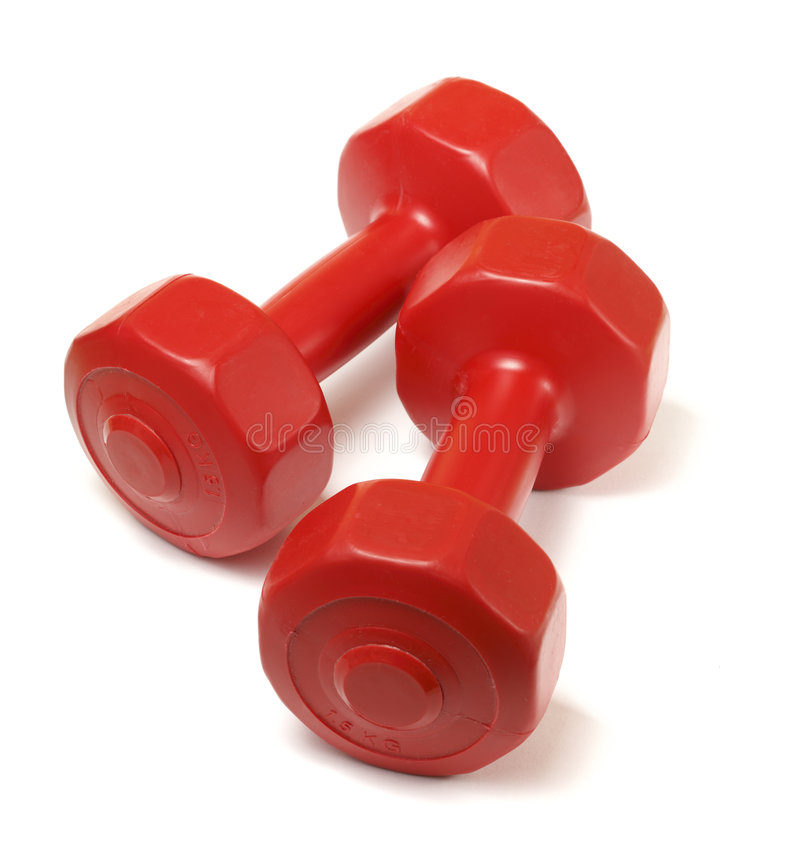 Dumbells. Red small plastic dumbells on white surface royalty free stock image