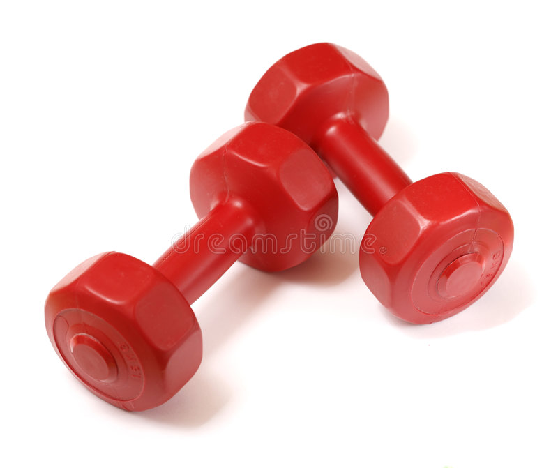 Dumbells. Small red 1, 5kg (3 lbs. ) plastic dumbells on white stock photography