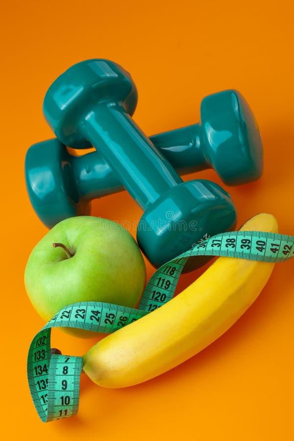 Dumbells com fita e frutas de medição foto de stock