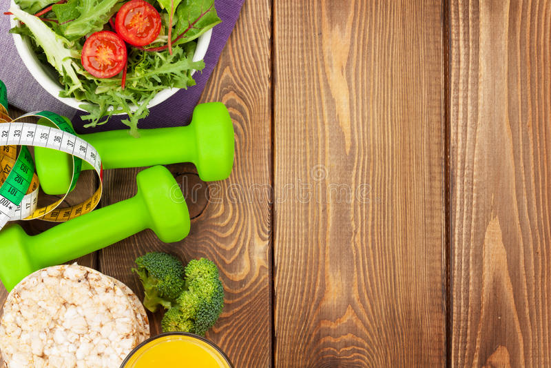 Dumbells, meetlint en gezond voedsel over houten lijst stock afbeeldingen