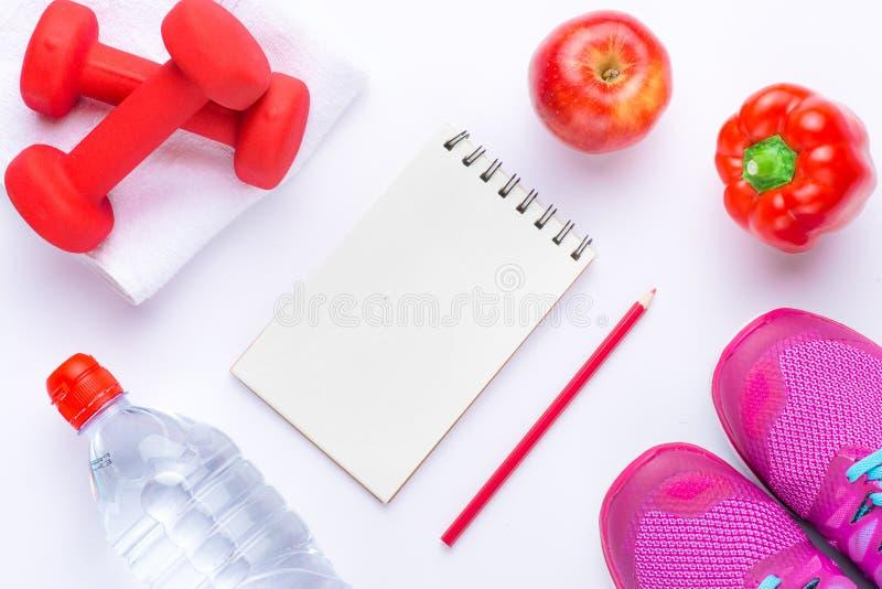 Dumbells, misura di nastro, alimento sano e blocco note per lo spazio della copia Forma fisica e salute Isolato su priorità bassa immagine stock