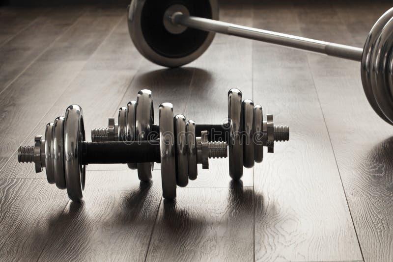 Dumbells per forma fisica sul pavimento di legno fotografia stock libera da diritti