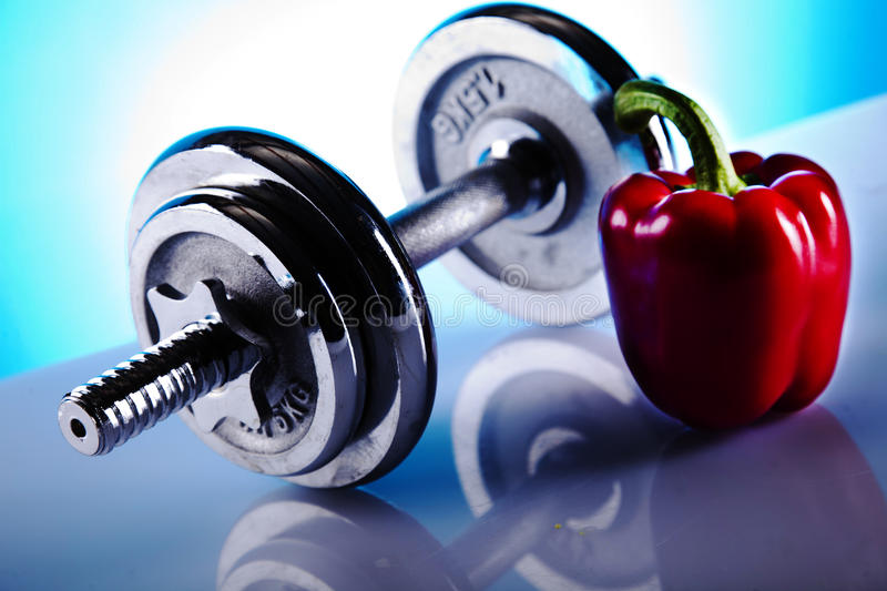 Dumbells and red paprika. On the blue background royalty free stock photo