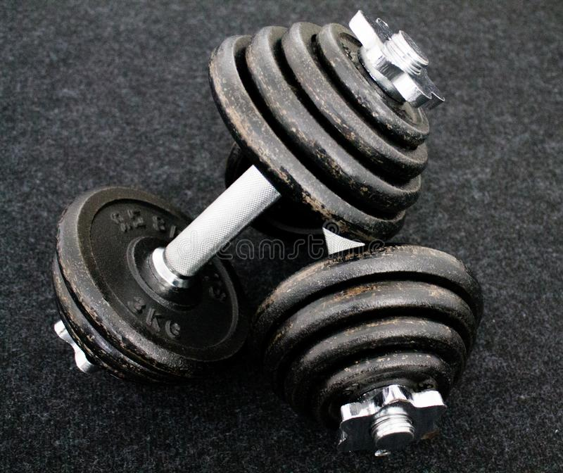 Dumbells set on the floor. Dumbells set laying on the floor with a black background stock photos