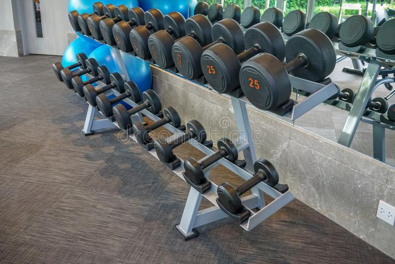 Dumbells set left on the racks in the gym. Healthy or sport concept stock photos