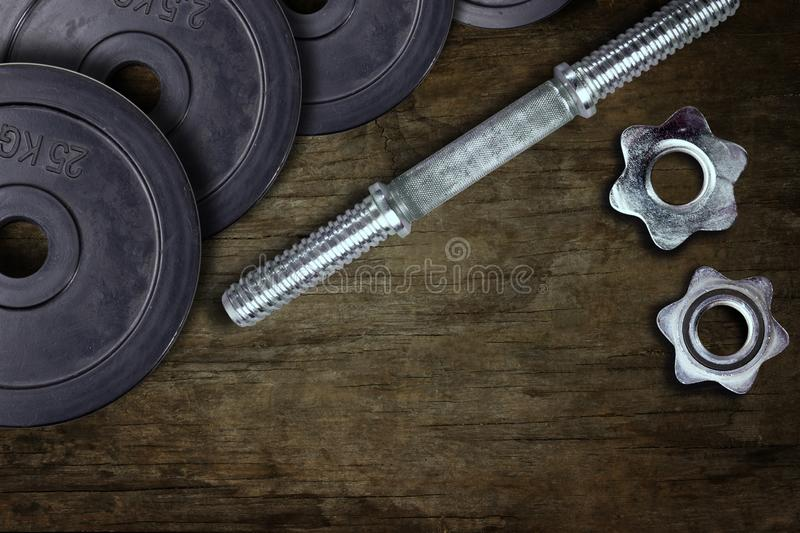 Dumbells and weights on the wooden floor. Fastening screws and barbells stock photos