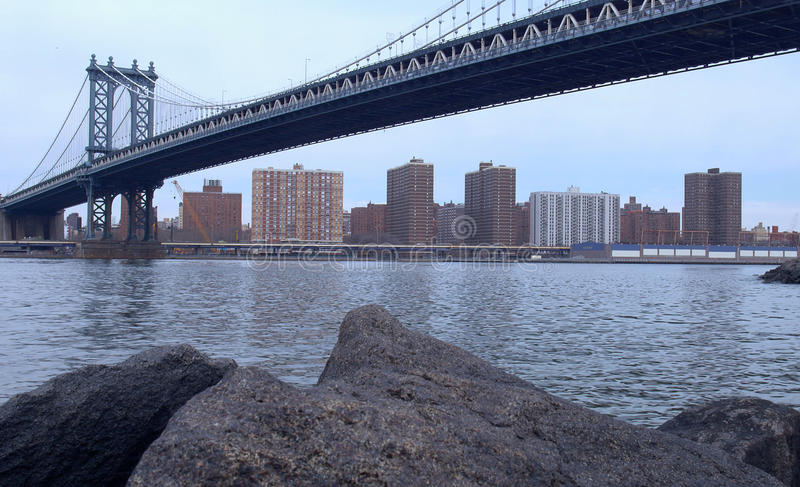 Dumbo Beach. View of the East River Under the Manhattan Bridge. View of the East River passing beneath the Manhattan Bridge and from above the rocks at Dumbo royalty free stock photos