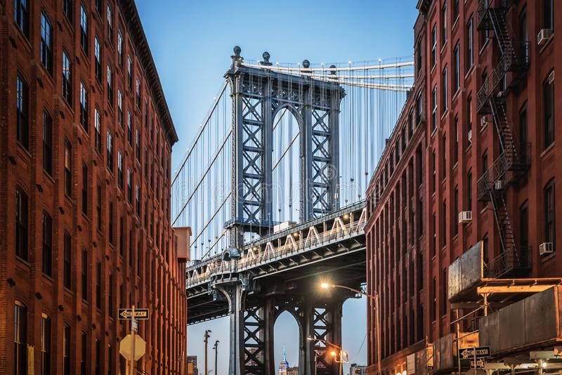 Dumbo - The famous Manhattan bridge between two red brick buildings in Brooklyn. In the evening stock photography