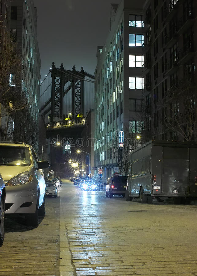 DUMBO New York City Night USA. Late night at the office. Washington Street view of Mahattan Bridge backlit by illuminated cloud above Empire State Building royalty free stock photo