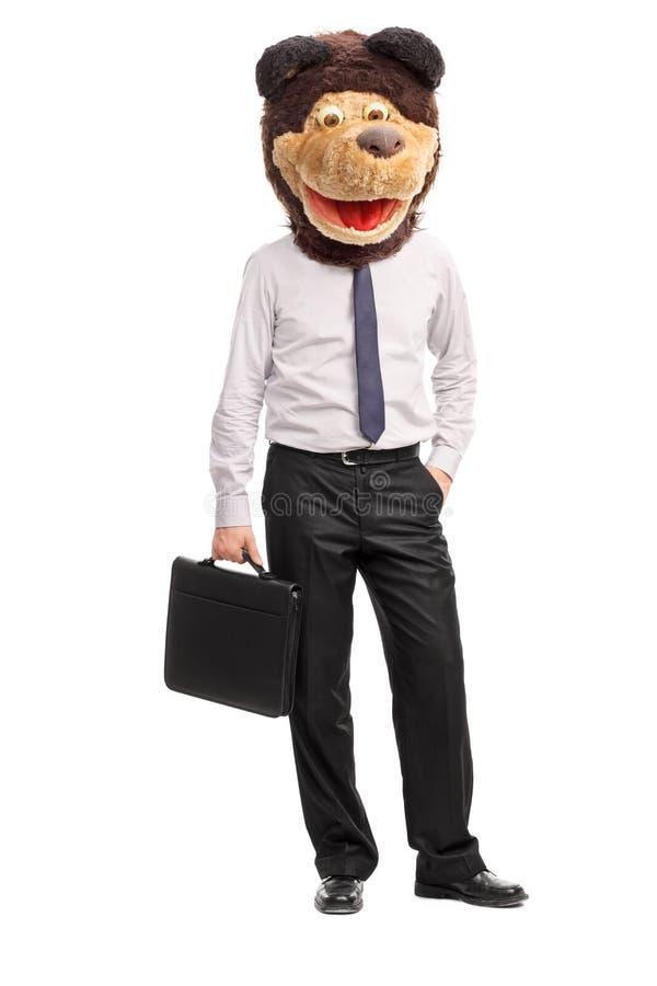 Dummer Geschäftsmann, der eine kindische Bärnmaske trägt lizenzfreie stockbilder