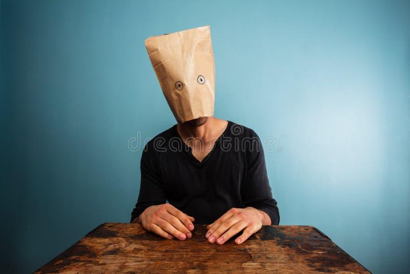 Dummer Mann mit Tasche über seinem Kopf stockbilder