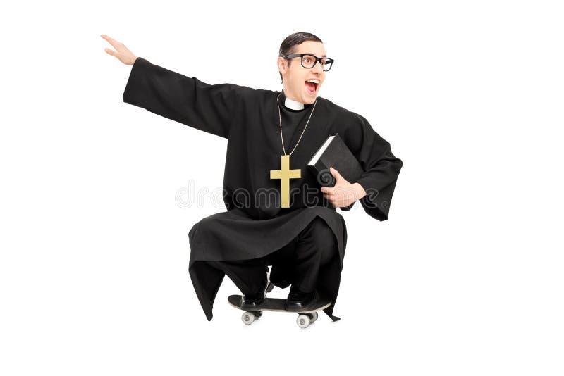 Dummer Priester, der ein kleines Skateboard reitet stockbilder
