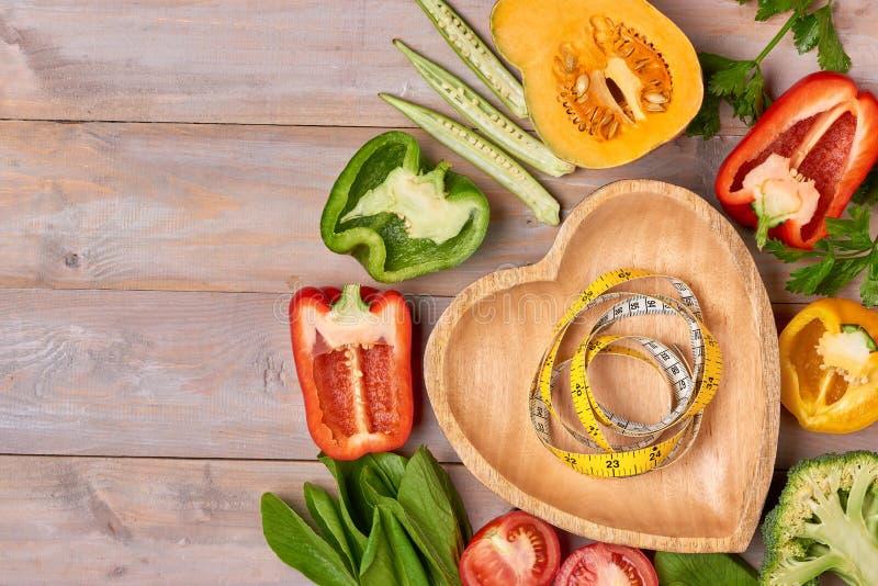 Dummkopf, Gemüsesalat und messendes Band auf rustikalem hölzernem ta stockfotografie