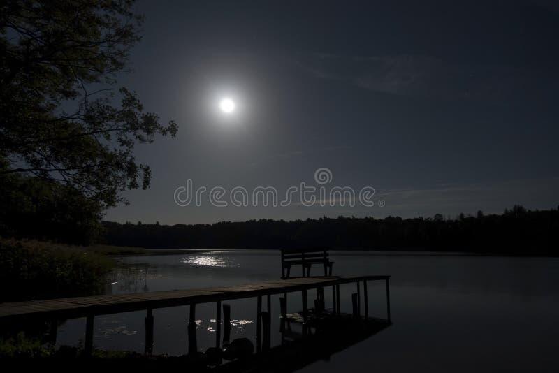 Dummkopfmond auf Waldsee mit Brücke lizenzfreie stockfotos