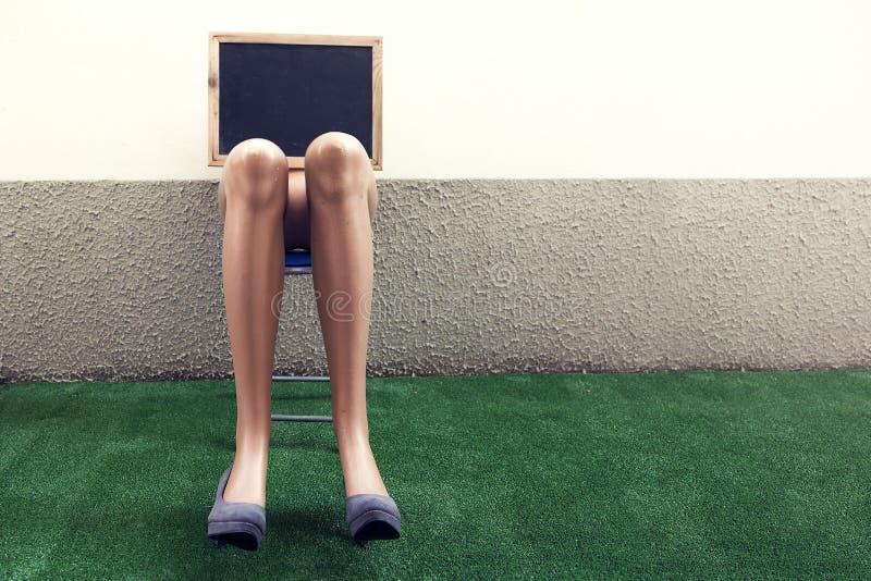 Dummy legs resting on a chair stock photos