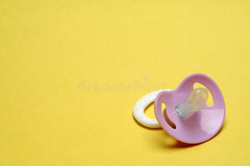 Dummy Pacifier on Yellow Background royalty free stock photo