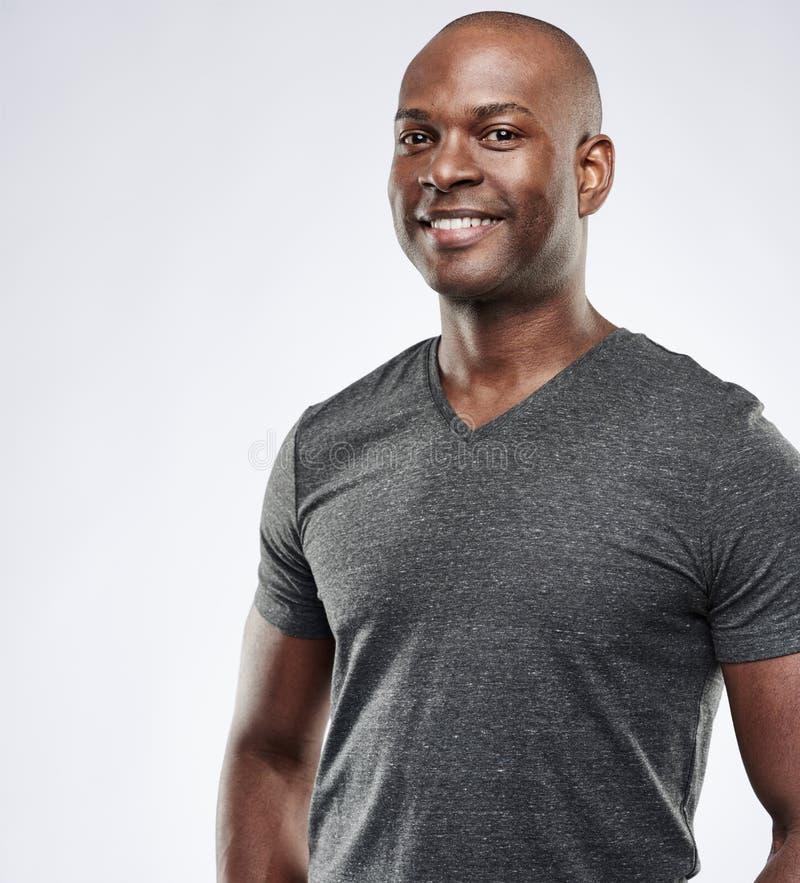 Dumny mięśniowy Afrykański mężczyzna z przyjemnym uśmiechem zdjęcia stock