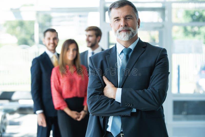 Dumny, uśmiechnięty biznesmen, stojący z kolegami w biurze obraz stock