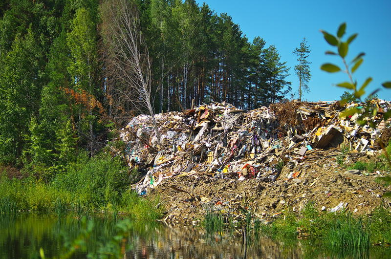 Dump construction waste absorbs nature. Forest lake and beautiful trees killed by mass construction landfill. Outskirts of the major Russian cities royalty free stock images