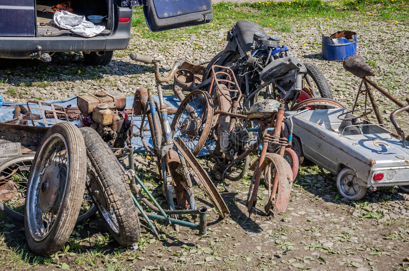 Dump the old broken rusty bicycles, motorcycles, toy cars, engines, tires and wheels with spokes in the open air on the ground stock photo