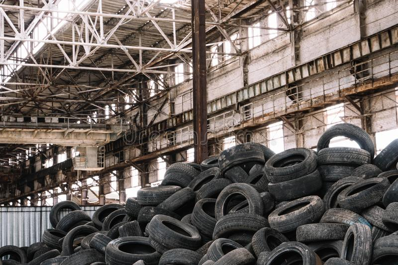 Dump of old used car tires at an factory stock photos