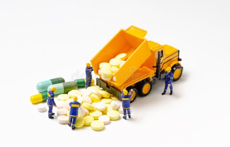 Dump trailer truck dumping drug to ground. Miniature technician team with a dump trailer truck dumping drug to ground stock photo