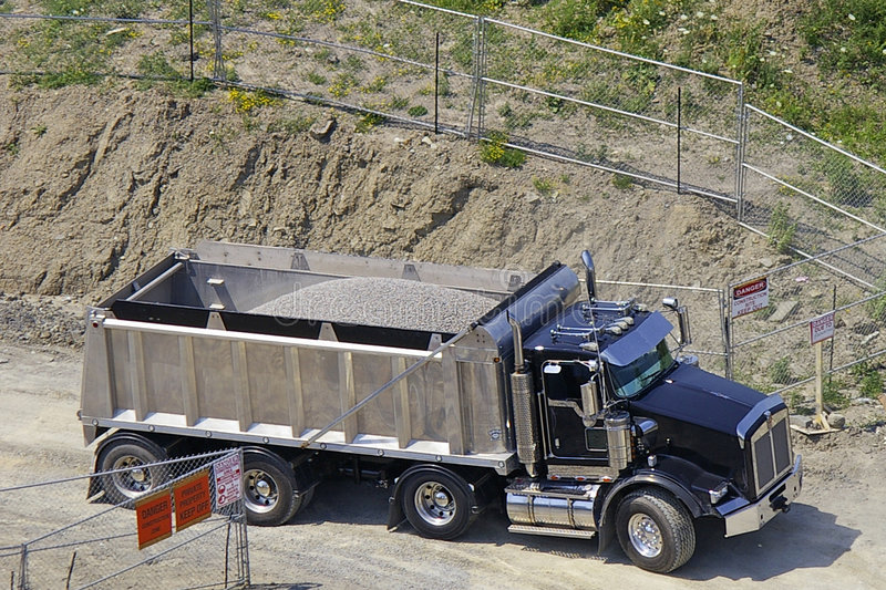Dump Truck backing in to Construction Site. A dump truck full of gravel backing into a construction site entrance royalty free stock photo