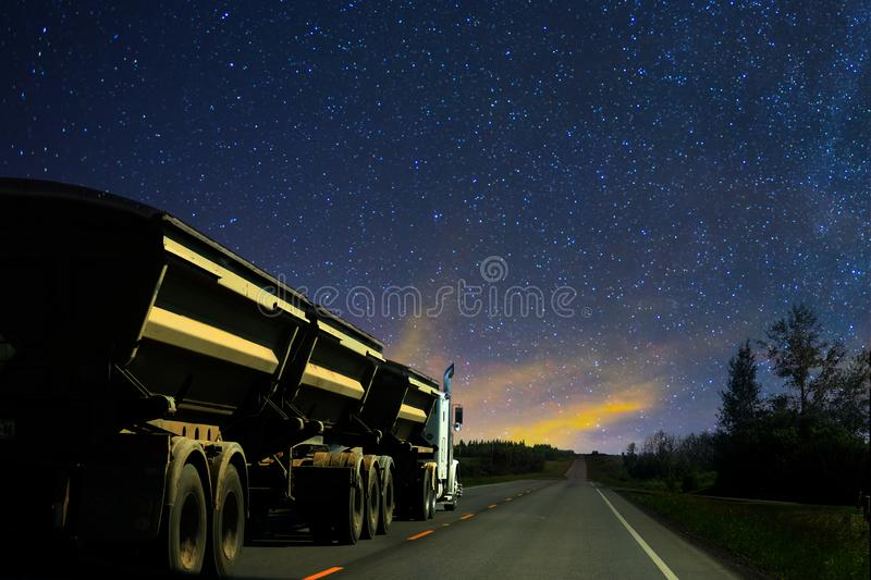 Dump truck big rig semi truck and trailer driving on a highway at night. Under the stars stock photos