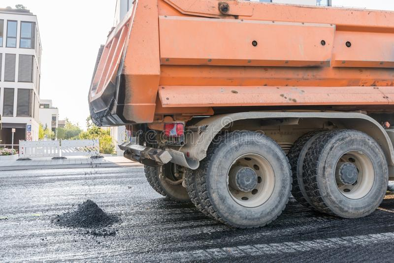 A dump truck brings hot asphalt for the renewal of a road pavement, Germany.  royalty free stock photography