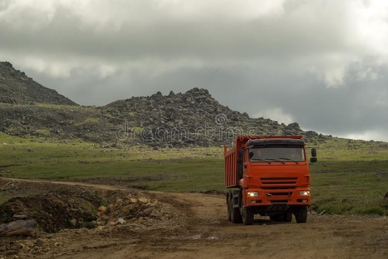 Dump truck is driving on a mountain road. Dump truck rides on the mountain road under construction royalty free stock photo