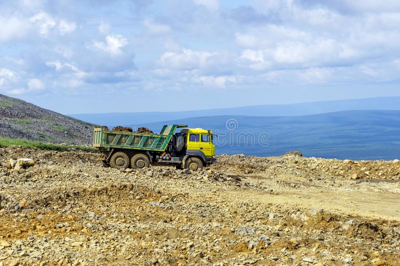 Dump truck is driving on a mountain road. Loaded dump truck rides on the mountain road under construction stock image