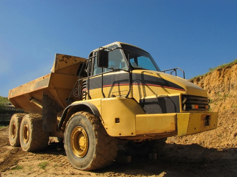 Dump Truck Front. A large yellow dump truck sits on a site ready for work stock images