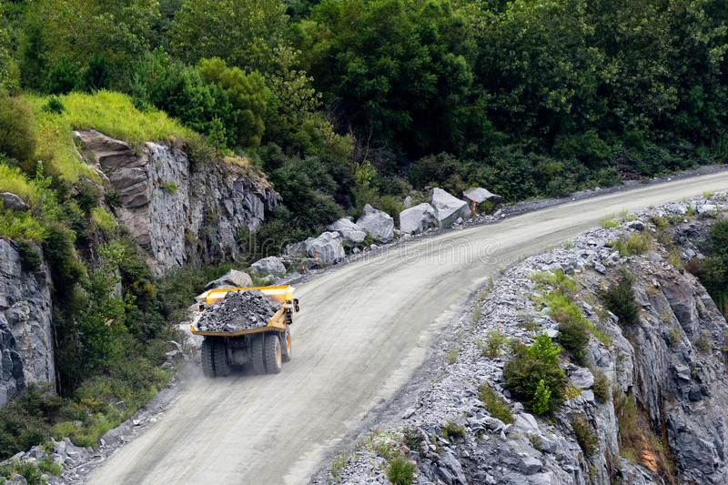 Dump truck hauling rocks in a mining and construction site. royalty free stock photos