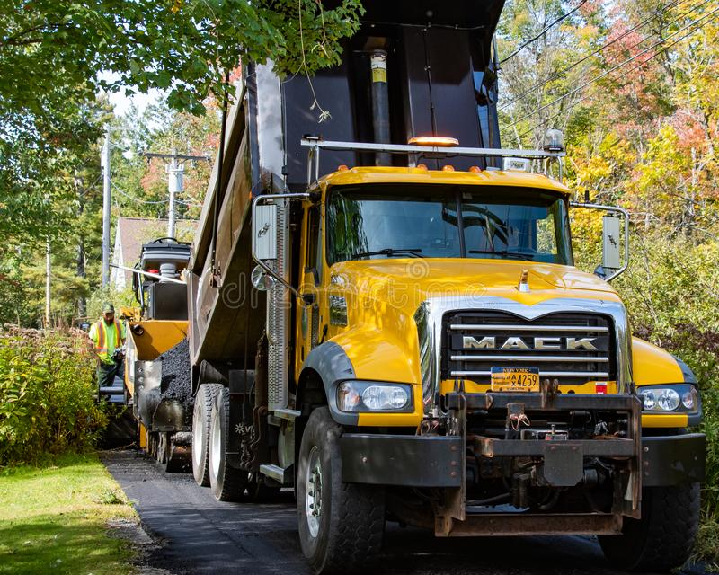 Dump truck and paving machine royalty free stock photos