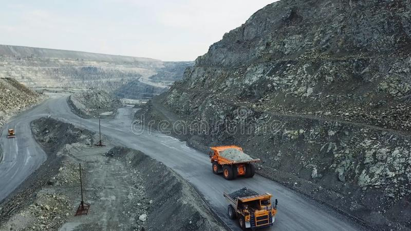 Dump truck is at quarry. Top view of driving orange dump truck with rubble on road open pit. Heavy transport in mining. Industry royalty free stock photos
